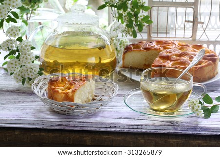 Pie with apricots and tea in a transparent teapot on a wooden table