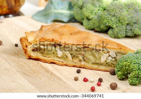 Pie with broccoli on a wooden table with fresh vegetebles and spices
