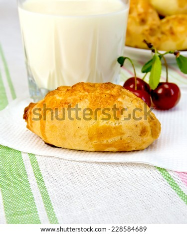Pie with cherries on a paper napkin, a glass of milk on a linen tablecloth background - stock photo