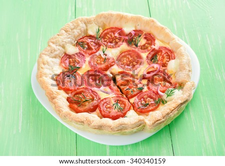 Pie with cherry tomatoes and curd cheese on green table - stock photo