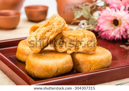 pie with meat wool, meat floss, pork floss, flossy pork, pork sung or yuk sung, is a dried meat product with a light and fluffy texture similar to coarse cotton, this pie is a dessert from China. - stock photo