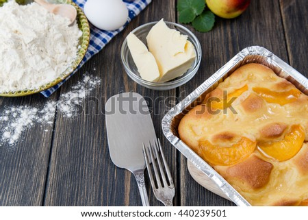 Pie with peaches on an old wooden table with green leaves, rustic style