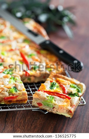 Pie with salmon, red pepper and broccoli, selective focus - stock photo