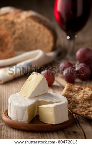 Piece and wheel of traditional Normandy soft cheese Camembert with country homemade bread, grapes and glass of red wine on wooden table - stock photo
