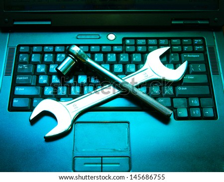 Piece blue and black laptop with a spanner on the keyboard - stock photo