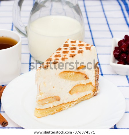 piece Italian Cake (dessert) tiramisu on a white plate. Cinnamon, a cup of tea (coffee), jug with milk and cinnamon sticks