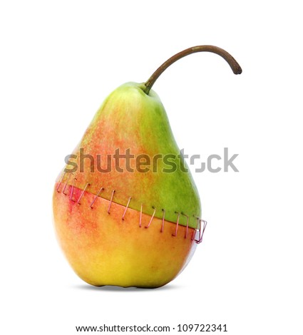piece of an apple and a pear stapled together symbolizing the negative aspects of genetic engineering. - stock photo