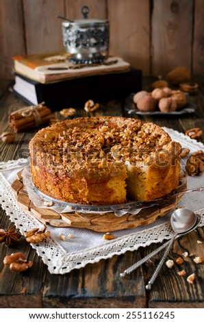 Piece of apple pie with walnut and sugar glaze on a wooden table - stock photo