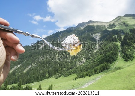 """Piece of austrian sweet scrambled eggs specialty"""" Kaiserschmarrn """", taken with a fork with mountains in the background. - stock photo"""