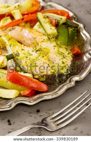 piece of baked fish and vegetables in a plate - stock photo