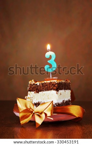 Piece of Birthday Chocolate Cake with Burning Candle as a Number Three on Brown Background - stock photo