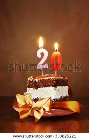 Piece of Birthday Chocolate Cake with Burning Candle as a Number Twenty on Brown Background - stock photo