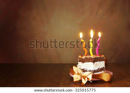 Piece of birthday chocolate cake with burning candles against brown background - stock photo