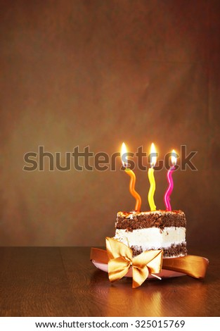 Piece of birthday chocolate cake with three burning candles against brown background - stock photo
