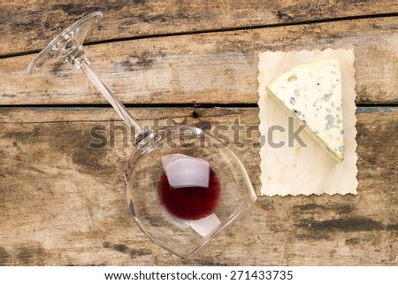 Piece of blue cheese with glass of wine on wooden table. Cheese with mold and overturned wineglass - stock photo