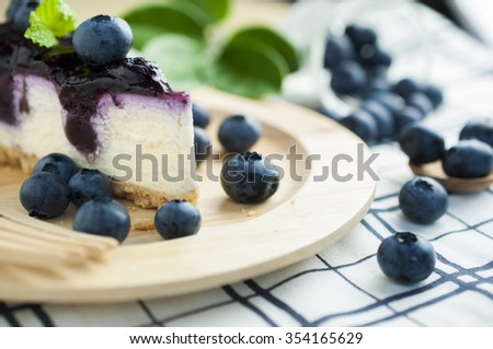 Piece of blueberry cheesecake on wooden plate with plenty of blue berries  - stock photo
