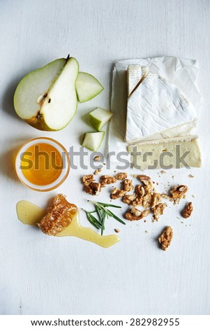 piece of brie, pear, honey and walnuts over white - stock photo