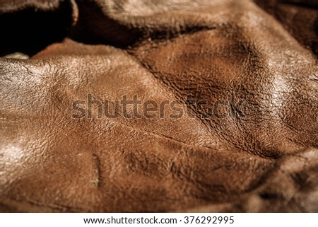Piece of Brown Leather and Suede Cut on Wood Table Workspace. Concept and Idea of Fine Leather Crafting, Handmade, Handcrafted and Leather Works. Background Textured and Wallpaper. Rustic Style. - stock photo