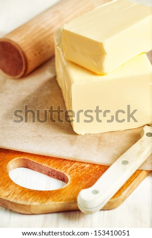 Piece of butter on paper and knife - stock photo