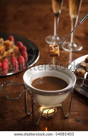 piece of cake dipped into a chocolate fondue - stock photo