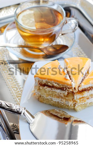 Piece of cake with apricot and tea on tray - stock photo