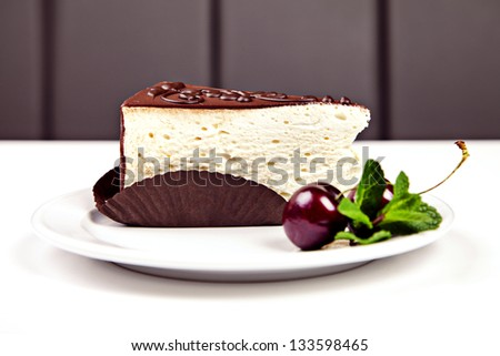 Piece of cake with chocolate, cherry and mint on white table - stock photo