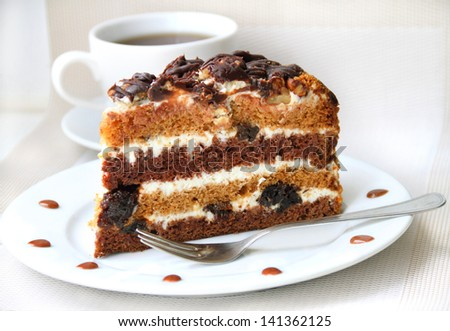 Piece of cake with cream, prunes and walnuts