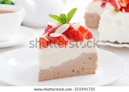 piece of cake with whipped cream, strawberries and tea, close-up - stock photo