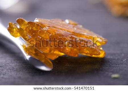 Piece of cannabis oil concentrate aka shatter with dabbing tool over dark background