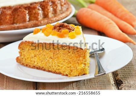 Piece of carrot cake with icing decorated dried apricots and walnut on white plate on rustic table - stock photo