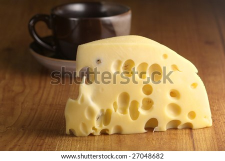 Piece of cheese close-up and dark cup on brown wood surface.