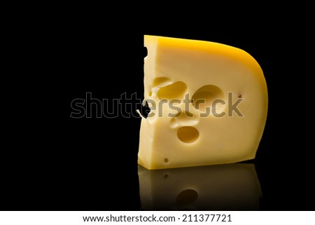 Piece of Cheese on Black Background - stock photo