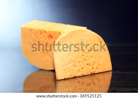 Piece of cheese on nice dark background with reverberation - stock photo