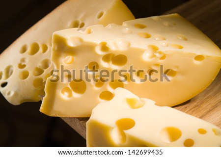 piece of cheese on wooden table - stock photo