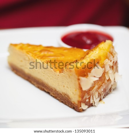Piece of cheesecake served on white plate with some fruit jam