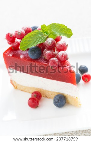 piece of cheesecake with berry jelly on a white plate, vertical, close-up - stock photo