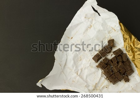 piece of chocolate bar in wrinkled golden paper wrapping on black background - stock photo