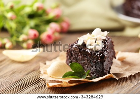 Piece of chocolate cake decorated with flowers on brown wooden table - stock photo
