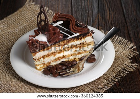 Piece of chocolate cake in plate on dark wooden background