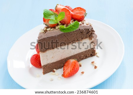 piece of chocolate cake of three layers on plate, close-up - stock photo