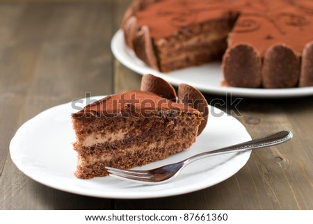 Piece of chocolate cake on a wooden table with the whole cake in the background - stock photo