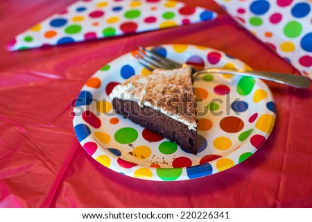 Piece of chocolate cake on party plate - stock photo