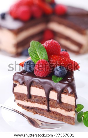 Piece of chocolate cake with icing and fresh berry - stock photo