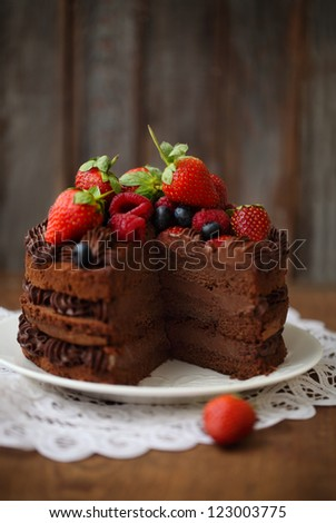 Piece of chocolate cake with icing and fresh berry on wooden background - stock photo