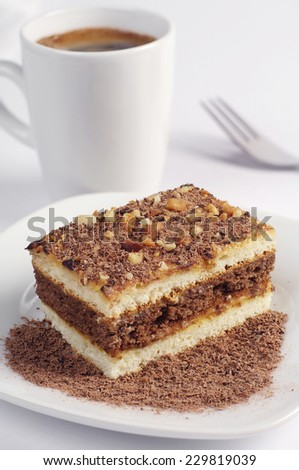 Piece of chocolate cake with nuts and coffee cup on white