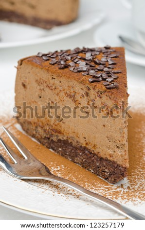 piece of chocolate cheesecake sprinkled with cocoa and a fork on a white plate - stock photo