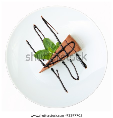 piece of chocolate cheesecake with mint petal on a white circular plate isolated on white background. Top view. - stock photo