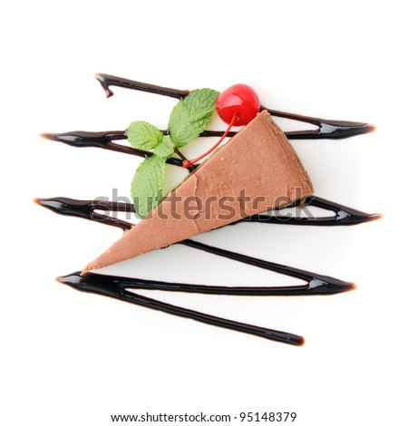 piece of chocolate cheesecake with mint twig and cherry on white background. Top view. - stock photo