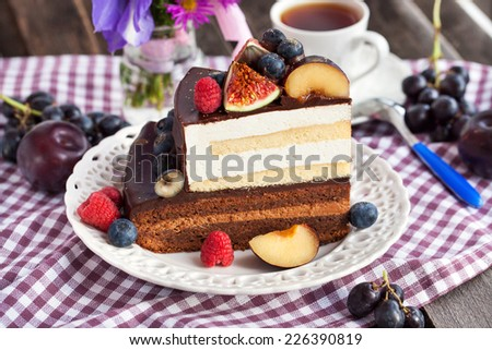 Piece of chocolate layer cake with cream and fresh fruit - stock photo