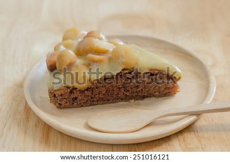 Piece of chocolate macadamia cake on wooden plate - stock photo